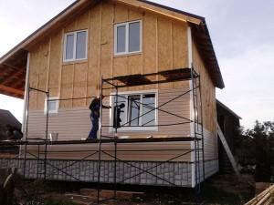 Вид на каркасный дом в процессе обшивания сайдингом